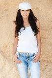 Slender brunette white cap jeans Stock Photos