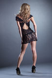 Slender curly blonde posing in black lace negligee Stock Photo