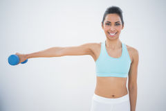 Slender dark haired woman lifting blue dumbbell Stock Photo