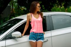 Slender fashionable brunette in a pink t-shirt and shorts standing near the car Stock Photo