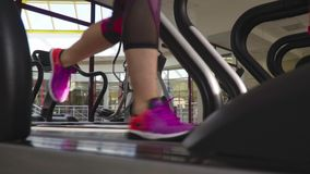 Female feet in sneakers and leggings run on a treadmill in the gym, slow motion. Slender female legs in sneakers and sport leggings that run on a treadmill, slow stock video footage