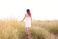 The slender figure  girl running hot summer afternoon, in a dress, concept  happiness, pleasure, sunrise and sunset, one. The slender figure of the girl running Royalty Free Stock Photos