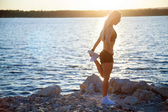 Slender fit woman on rocky beach stretching after workout Royalty Free Stock Photography