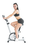Slender fit woman training on an exercise bike smiling at camera Stock Photos