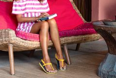 Slender foots of beautiful woman sitting on a pink sofa and keeping a book. Interior in ethnic style. Close up stock photos