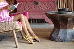 Slender foots of beautiful woman sitting on a pink sofa and reading a book. Interior in ethnic style. Close up stock photography