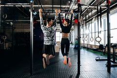Slender girl and athletic man dressed in sports clothes are pulling up on the bar in the gym stock image
