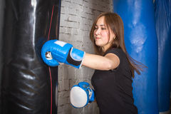 Slender girl boxing pear. She fulfills blows in the gym Royalty Free Stock Photos