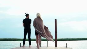 Slender girl in covering walking along wooden pier to her lover, man standing and fishing at lake stock video