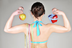 A slender girl holding an apple and red pepper royalty free stock photos