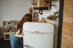 Slender girl in jeans opening retro fridge door and looking into fridge stock photo