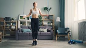 Slender girl in leggings and top jumping rope at home concentrated on activity