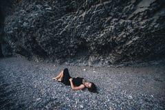 Slender girl in the long black dress lying on the pebbles near rock Stock Photo