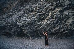 Slender girl in the long black dress standing near the rock Stock Photo