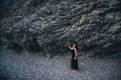 Slender girl in the long black dress standing near the rock Royalty Free Stock Images