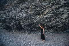 Slender girl in the long black dress standing near the rock. On the beach Royalty Free Stock Photos