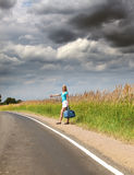 The slender girl with a long fair hair in a blue t-shirt and white shorts stops a passing car on the road to the summer day Stock Photo