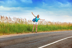 The slender girl with a long fair hair in a blue t-shirt and white shorts stops a passing car on the road to the sunny summer day Stock Images