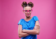 Slender girl in pink glasses with crossed hands over pink backgr Stock Image