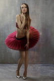 Slender girl in a red tutu and shoes stands on the background of Royalty Free Stock Images