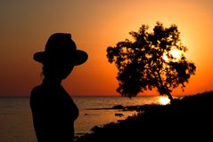 Slender girl silhouette against the sea sunset Stock Image
