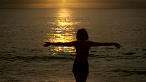 Slender girl slowly walks into the ocean at sunset to cool off. Silhouette of a young woman on a background of the sun stock video
