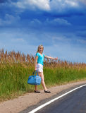 The slender girl stops a passing car on the road to the sunny summer day Stock Photography