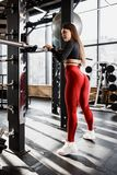 Slender girl in stylish bright sports clothes poses standing next to the horizontal bar with sport equipment around in royalty free stock photo