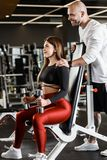 Slender girl in stylish sports clothes sits on a sports bench holding dumbbell in her hands and athletic man stands royalty free stock photography