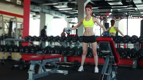Slender girl training with dumbbells in gym. View of slender girl training with dumbbells in gym stock video