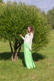 Girl by the tree. Slender girl by the tree in the summer park Royalty Free Stock Image