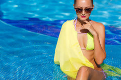 A slender girl with yellow pareo by the pool Stock Photos