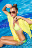 A slender girl with yellow pareo by the pool Stock Images
