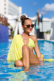 A slender girl with yellow pareo by the pool Stock Photography
