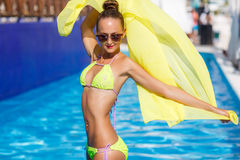 A slender girl with yellow pareo by the pool Stock Photo
