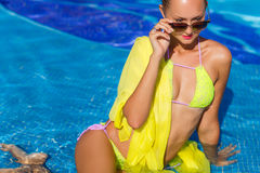 A slender girl with yellow pareo by the pool Royalty Free Stock Photos