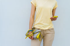Slender girl in a yellow T-shirt holding yellow lady's handbag a Stock Images