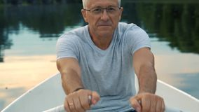 A slender gray-haired serious man in a gray t-shirt and glasses rowing on a white boat on a calm river on a summer stock video