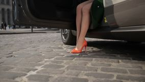 Slender lady legs in high heels getting out of car stock footage