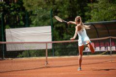 Slender lady is playing tennis on court stock images