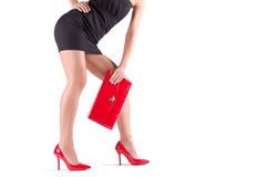 Slender legs in red shoes. Slender beautiful female legs in red shoes and mini bag Royalty Free Stock Photography