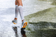 Slender legs of women marathoner in compression socks. Running through a puddle, water sprays stock photo