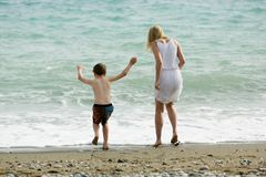 Blonde slim mother and her child enjoy together summer, waves of sea at beach. royalty free stock photo