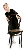 Slender little dancer posing near the old Vienna chair. Stock Image