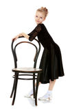 Slender little dancer posing near the old Vienna chair. Stock Images