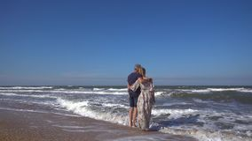 A slender man and a woman in a long dress stand embracing on a sandy beach in the rolling waves of the sea in the wind. Slender man and woman standing embracing stock video