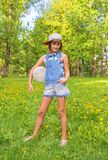 Slender, mischievous, provocative teenage girl i. N a baseball cap and overalls playing ball in the park Royalty Free Stock Image