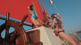 Slender model girls in bikini enjoying life. Driving on a yacht with red sails on the sea stock video