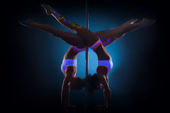 Slender pole dancers posing standing on hands Royalty Free Stock Images