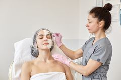 Slender professional cosmetologist applies moisturizing mask on clients face, covering half of face with white revitalizing cream. With cosmetological brush royalty free stock images